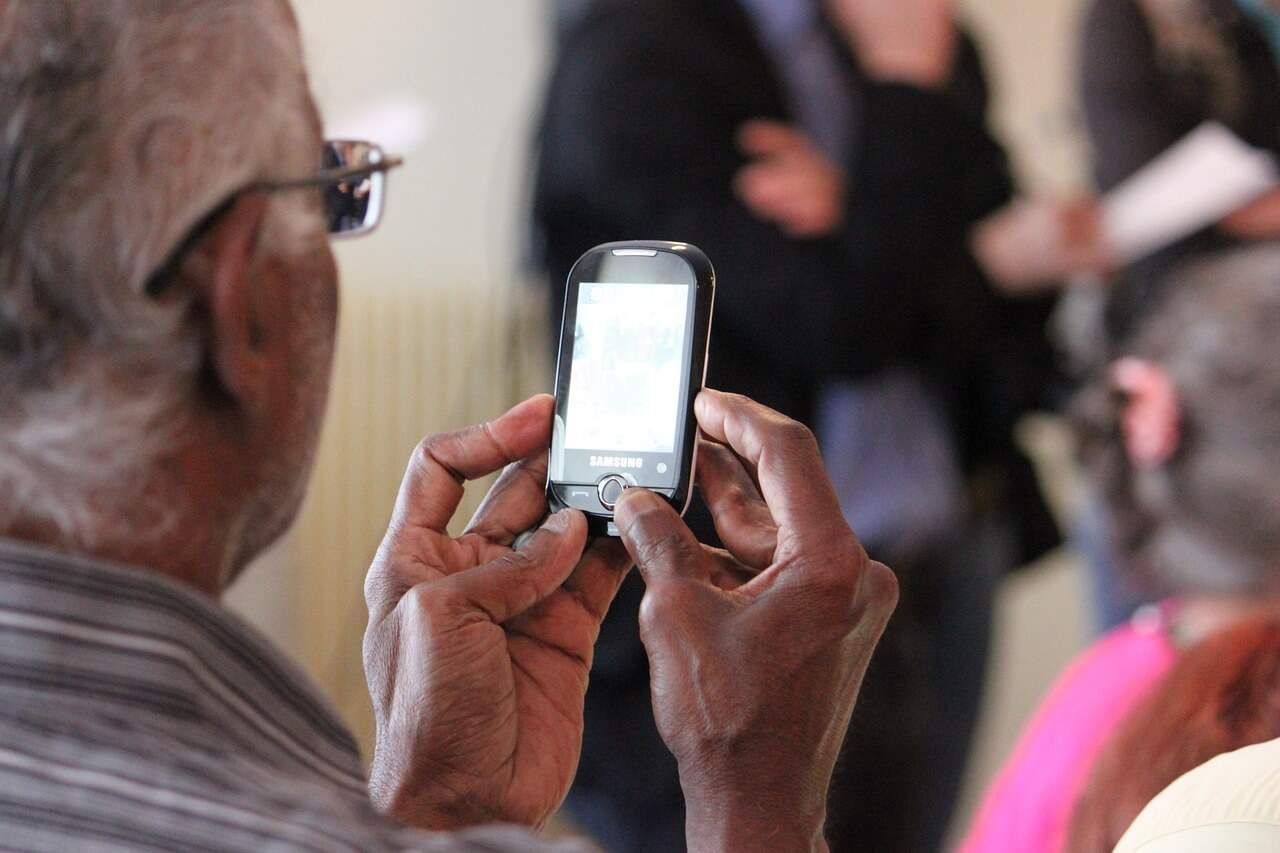 An older man looking at a cellphone.