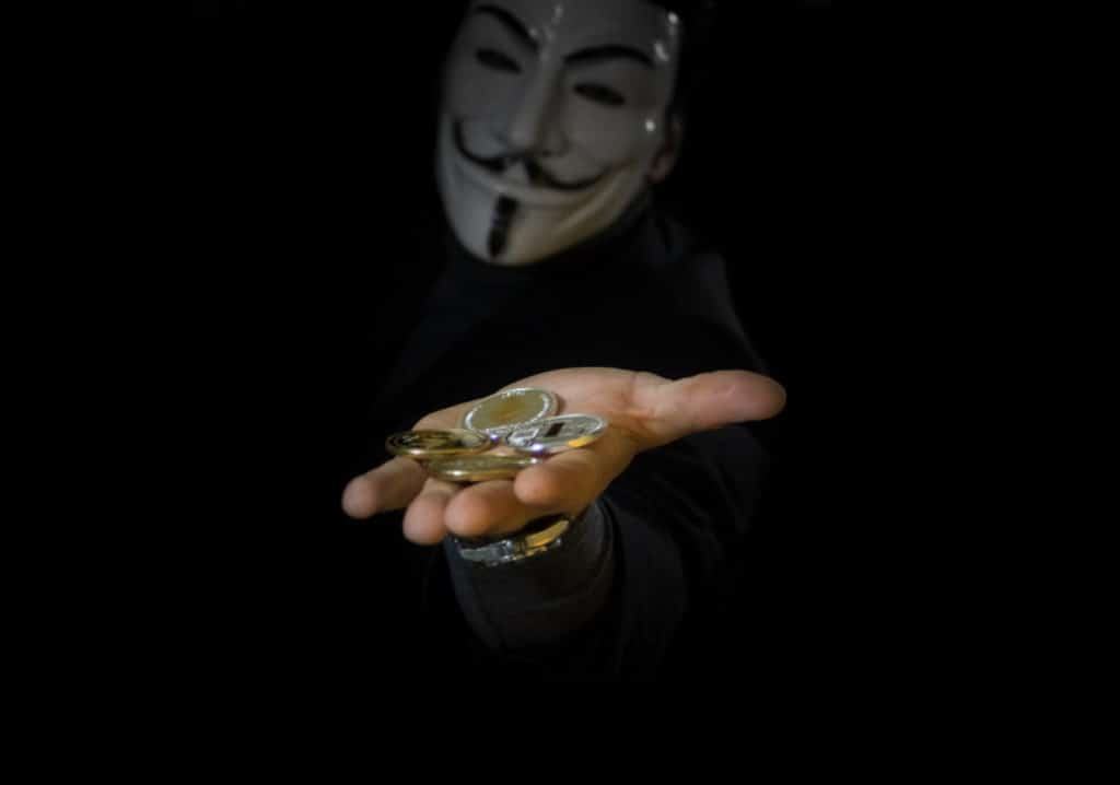 An outstreteched hand holding coins coming from a person wearing an 'anonymous' mask.